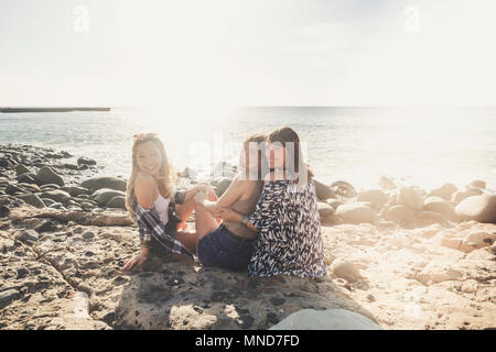 Group of beautiful woman young speaking and smiling aroud in a stone beach in Tenerife. team girls having fun together - Stock Photo
