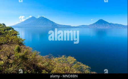 View from Lake Atitlan in the early morning, blue skys and clear water, beautiful magic lake with volcanos and indigenous people in the highland of Gu - Stock Photo