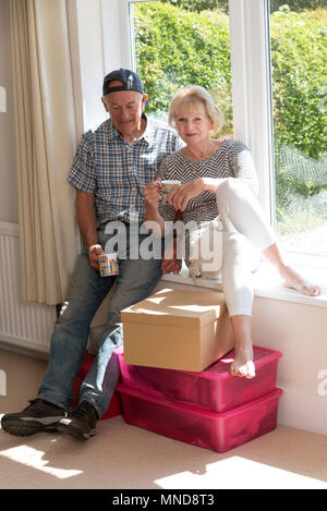 Moving house. Couple sitting on a window seat in their home relaxed and waiting for removal company - Stock Photo