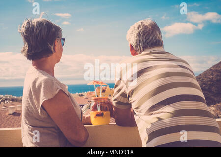 two elderly man and woman looking together the ocean view in vacation. Back view with roofs in vintage style. - Stock Photo