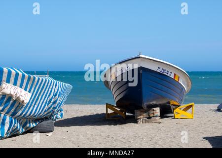 Fishing boat sitting on beach at promenade Torre del mar. Spain - Stock Photo