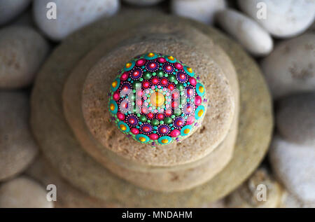 Beautiful hand painted mandala stone lies on the rocks - Stock Photo