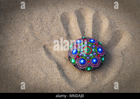 Hand painted mandala rock on the wake of a hand on the sand - Stock Photo