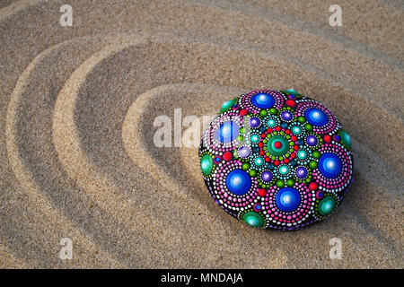 hand painted mandala rock on sand closeup - Stock Photo