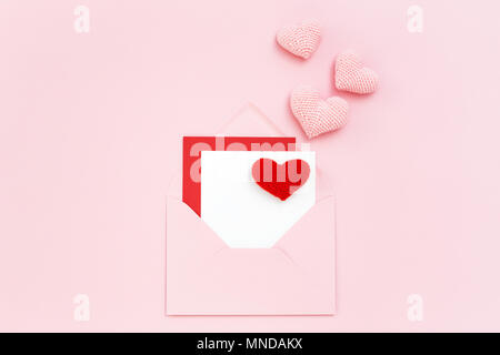 Valentine card in pink envelope with red & pink hearts. Minimal style greeting card. Birthday, Mothers day, Women's Day. Love letter. Copy space, flat - Stock Photo