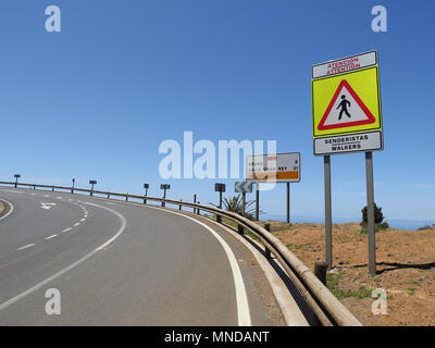 Footpath on a sharp bend of a major coastal road in northern La Gomera Canary Islands with clear pedestrian warning sign - Stock Photo