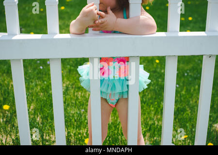 A faceless toddler girl wearing a bright colored bathing suit with flowers on it. - Stock Photo