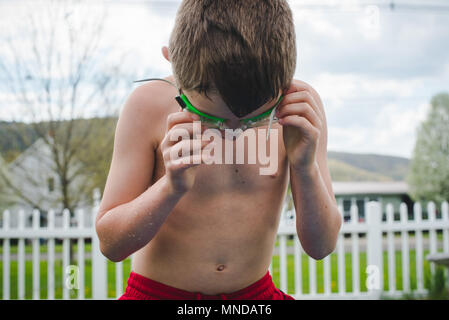 A boy wearing green swimming goggles on a sunny summer day - Stock Photo