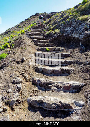 A female walker climbing a steep stepped path high above Hermigua on the north coast of La Gomera in the Canary Islands