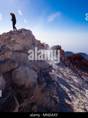 A female climber on the smouldering summit crater of active volcano Mount Teide at 3718 metres on Tenerife the largest of the Canary Islands - Stock Photo