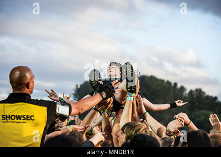 Girl crowd surfer lifted above the music festival crowd as security man watches on. - Stock Photo