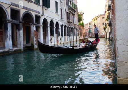 Tourists enjoy a gondola ride on a Venetian afternoon. - Stock Photo