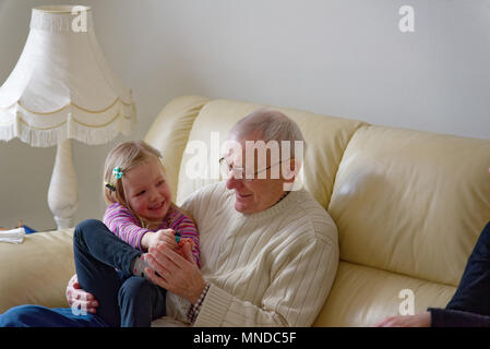 Grandfather and his three year old grand-daughter laughing together sat on a sofa - Stock Photo