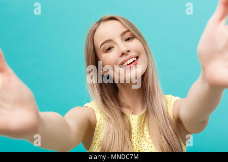 Close-up portrait of attractive young woman stretching her arms, wants to hug you. Isolated on blue background. - Stock Photo