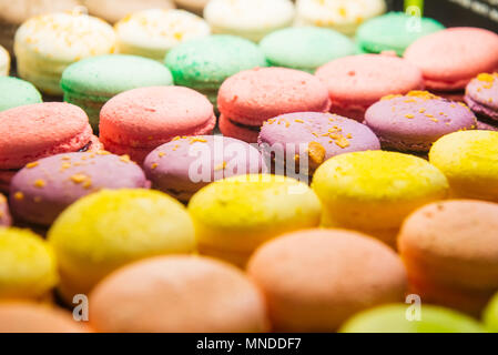 Assortment of Colorful macarons for sale in shop. Rows of macaroons in candy shop, storefront with sweets, cafe showcase. Traditional french almond ca - Stock Photo