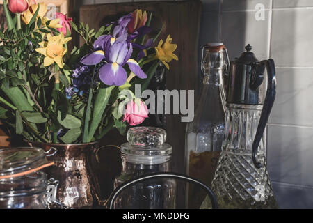 Bouquet of spring flowers in stylish kitchen,Uk.Kitchen decoration, still life composition, natural sunlight from window.Afternoon light.Cut flowers. - Stock Photo
