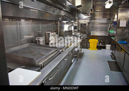 stainless steel surfaces and grills in an industrial sized kitchen - Stock Photo