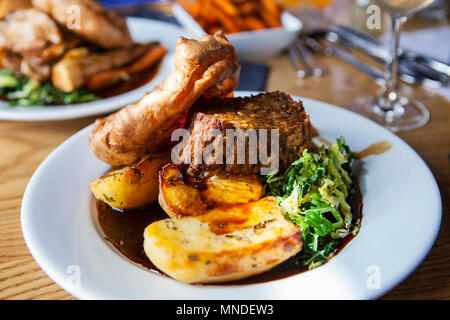 Vegetarian dinner with nut roast, potatoes, yorkshire pudding and gravy - Stock Photo