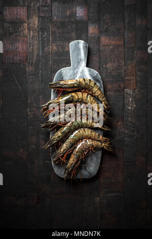 Raw prawns in shells on a stone board, top view. - Stock Photo