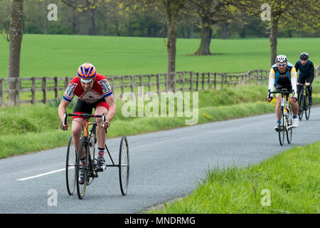 Close-up of mature man on tricycle, pedalling & cycling on scenic country lane, 2 men on bicycles behind - near Ilkley, North Yorkshire, England, UK. - Stock Photo