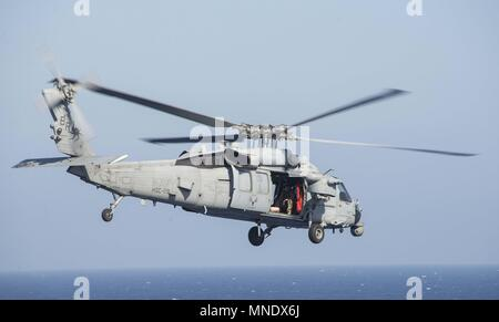 180515-N-AH771-0081 U.S. 5TH FLEET AREA OF OPERATIONS (May 15, 2018) An MH-60S Seahawk, attached to Helicopter Sea Squadron (HSC) 28, takes off from the flight deck of the Wasp-class amphibious assault ship USS Iwo Jima (LHD 7) during a replenishment-at-sea, May 15, 2018, May 15, 2018. Iwo Jima, homeported in Mayport, Fla. is on deployment to the U.S. 5th Fleet area of operations in support of maritime security operations to reassure allies and partners, and preserve the freedom of navigation and the free flow of commerce in the region. (U.S. Navy photo by Mass Communication Specialist 3rd Cla - Stock Photo