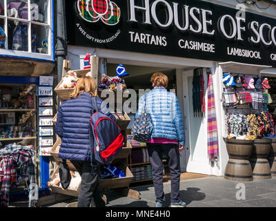 Royal Mile, Edinburgh, 16th May 2018. Tourists enjoying the sunshine on Royal Mile, Edinburgh, Scotland, United Kingdom. Tourists browse a souvenir shop called House of Scotland, with the usual tartan goods for sale - Stock Photo