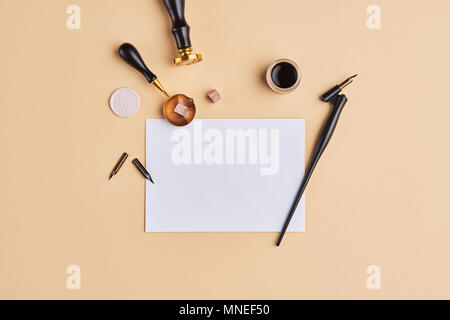 Flat lay of feminine desk workspace with copy space. Calligraphic style, paper on beige background. Top view of minimal composition with copy space. - Stock Photo