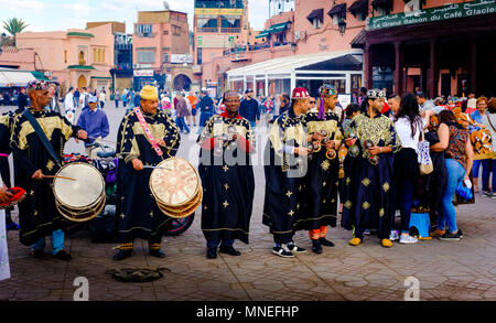 Percussionist in traditional costume entertaining tourists in the Jemaa El Fna, a world heritage site, Marrakech, Morocco - Stock Photo