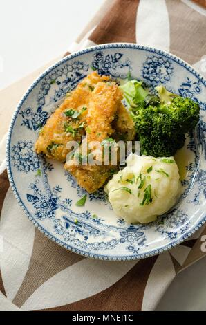 Breaded fish fillets with broccoli and mashed potatoes - Stock Photo