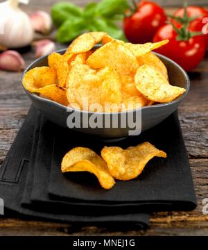 A bowl of tomato crisps - Stock Photo