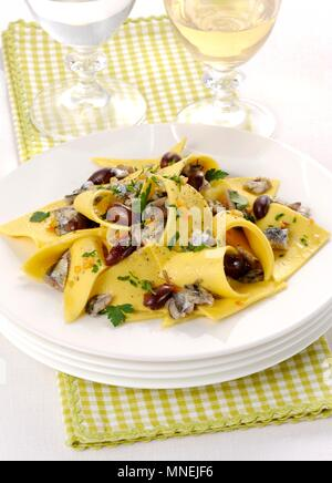 Stracci con alici (fresh pasta with anchovies and olives, Italy) - Stock Photo