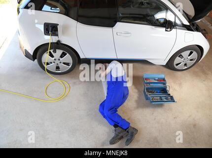 A Mechanic repairing an electric driven car at garage - Stock Photo