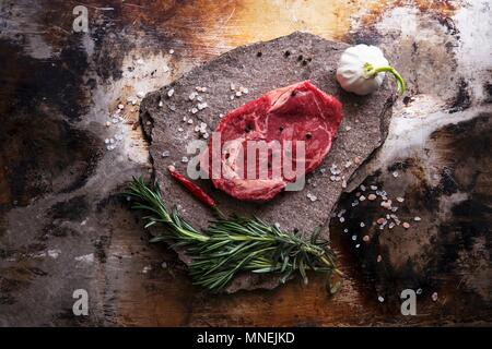 A beef steak, salt, garlic, a chilli pepper and herbs - Stock Photo