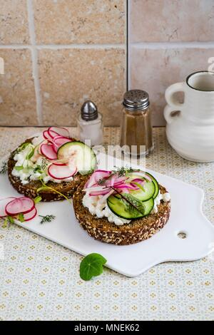 Open sandwiches with cream cheese, radishes and cucumber - Stock Photo