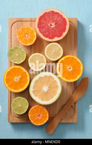 Halved citrus fruits on a wooden board - Stock Photo