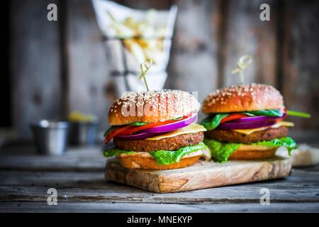 Homemade burgers on rustic wooden surface - Stock Photo