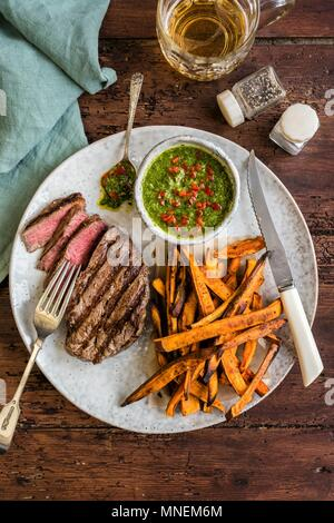 Griddled fillet steak with sweet potato fries and chimichurri sauce - Stock Photo