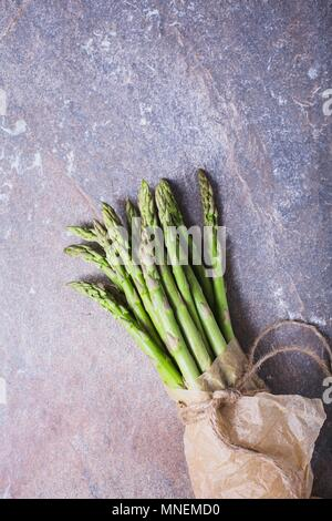 A bunch of fresh asparagus spears in a paper bag tied with string - Stock Photo