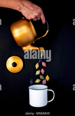 Shell pasta being poured from a teapot into an enamel mug - Stock Photo