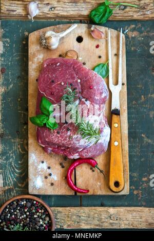 Raw pork with herbs, garlic, pepper and chilli on a chopping board - Stock Photo
