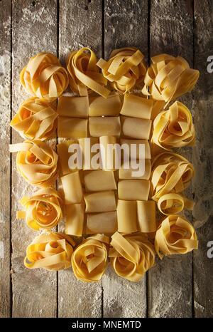 Italian pastas with flour on a wooden table - Stock Photo