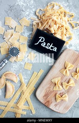 Different varieties of homemade pasta with a small wooden board, a pastry wheel, and a 'Pasta' sign - Stock Photo