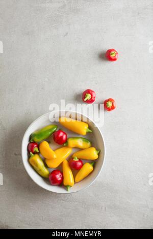 Red, yellow and green mini peppers in a bowl and next to it - Stock Photo