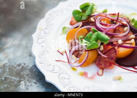 Blood orange salad with red onions and pine nuts - Stock Photo