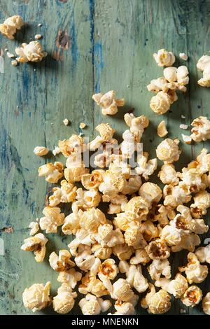 Popcorn covering an aqua blue green wooden surface - Stock Photo