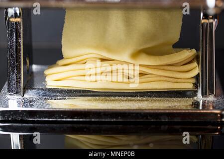 Fresh pasta dough being passed through a pasta machine - Stock Photo