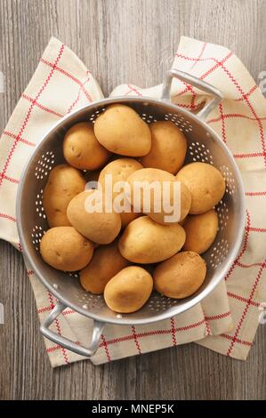 Potatoes in a colander on a tea towel - Stock Photo