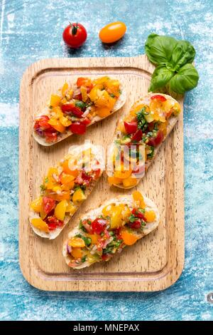 Bruschetta with colourful tomatoes and basil - Stock Photo