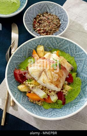Cod wrapped in bacon on a bed of vegetables and couscous with green sauce - Stock Photo