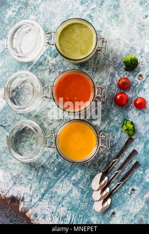 Various colourful soups in glass jars (broccoli soup, tomato soup, pumpkin soup) - Stock Photo
